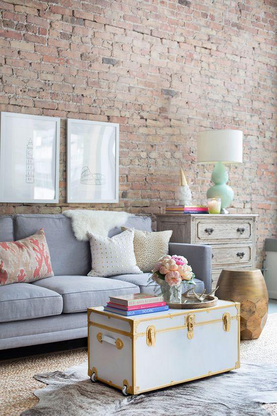 Sala vintage decorada com papel de parede de tijolinh e bau de madeira azul e dourado no centro do ambiente