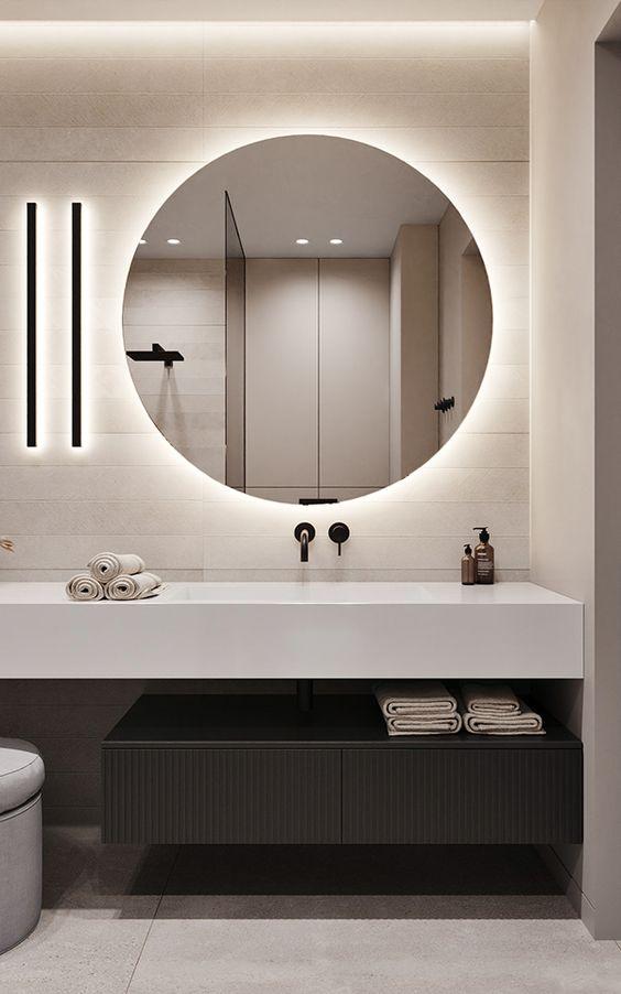 Silestone branco com espelho redondo iluminado na decoração moderna