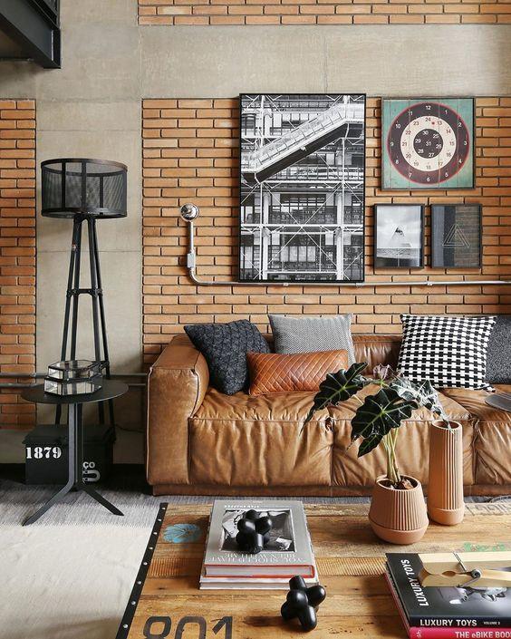 Sofá estilo industrial de couro e parede de tijolinho