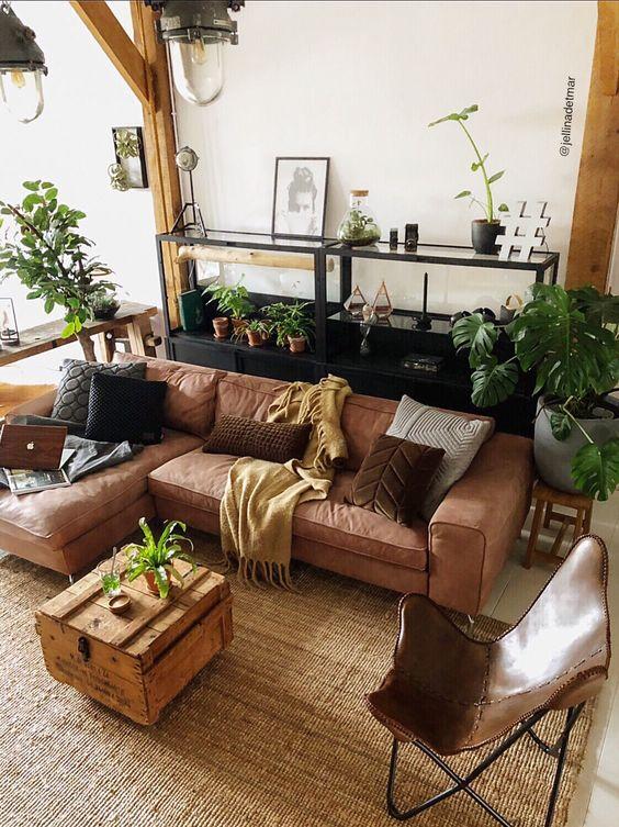 Sofá estilo industrial marrom na sala decorada com plantas