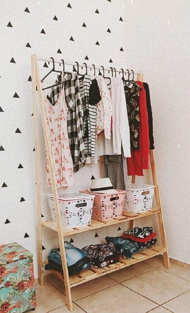 Use cestos para organizar a arara de roupas em madeira. Fonte: Pinterest