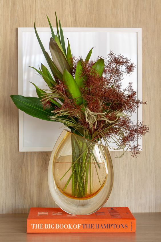 Vaso de flor com livro laranja para decorar a estante