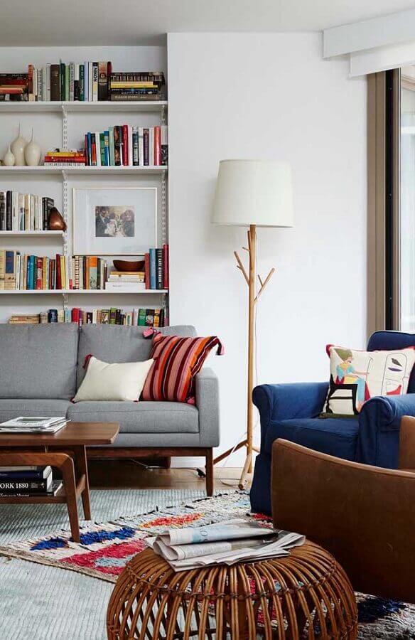 abajur de pé para sala decorada com estante de livros e poltrona azul Foto Jeito de Casa