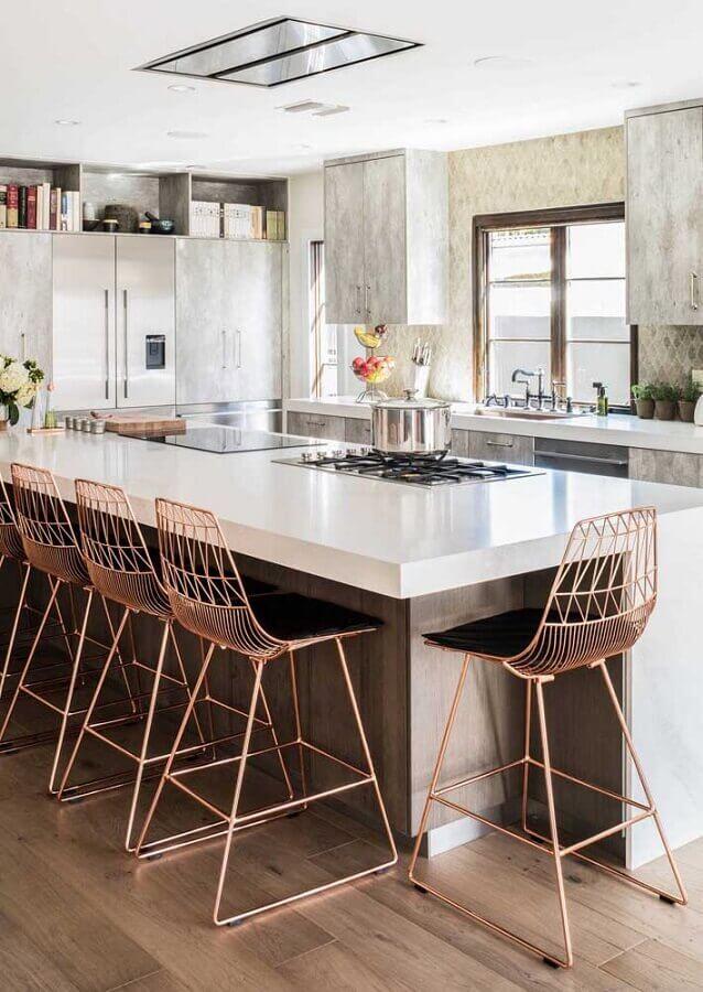 Bancada branca com cooktop e banquetas rose gold