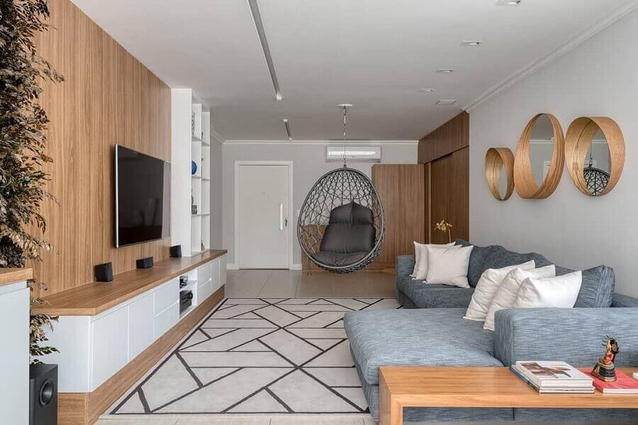 cadeira de balanço moderna suspensa para sala de TV decorada com painel de madeira e sofá cinza  Foto Flávia e Letícia Abaurre
