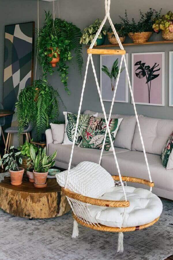 cadeira de balanço suspensa para sala cinza decorada com vasos de plantas e mesa de centro rústica Foto Pinterest