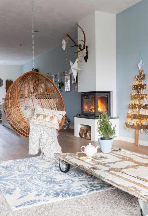 Cadeira de balanço suspensa para sala com lareira decorada com mesa de centro rústica  Foto Editions de l'Arkhan