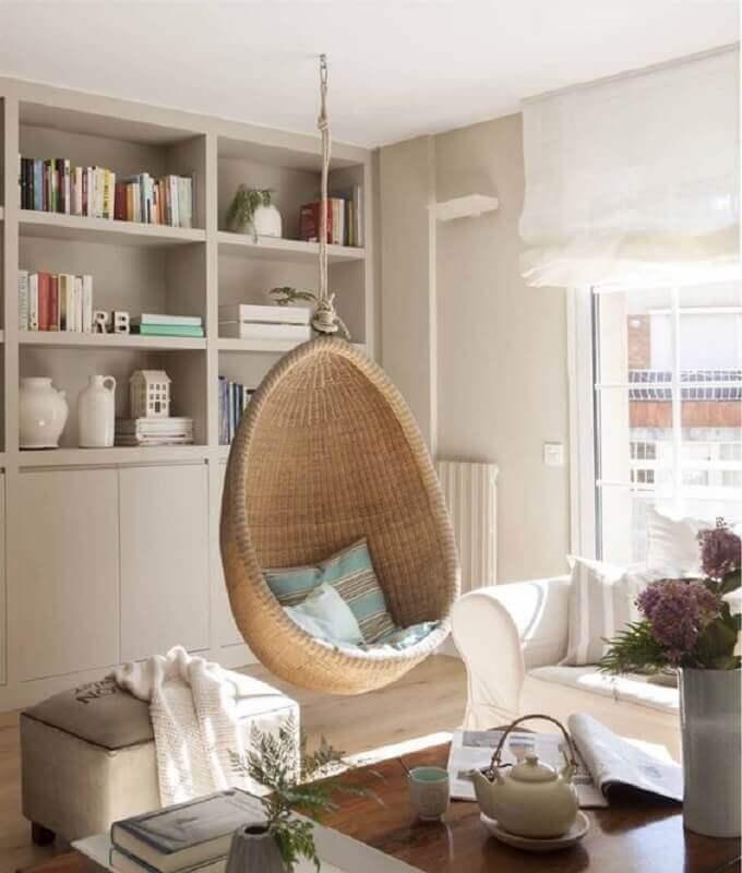 Cadeira de balanço suspensa para sala de estar decorada em cores neutras  Foto El Mueble