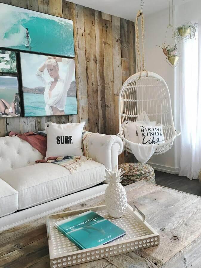 Cadeira de balanço suspensa para sala decorada com sofá branco e parede rústica de madeira Foto Billabong Women's