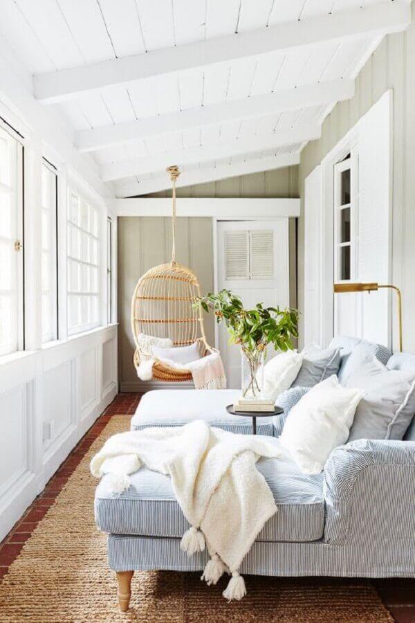 Cadeira de balanço suspensa para sala pequena decorada com sofá confortável Foto domino magazine