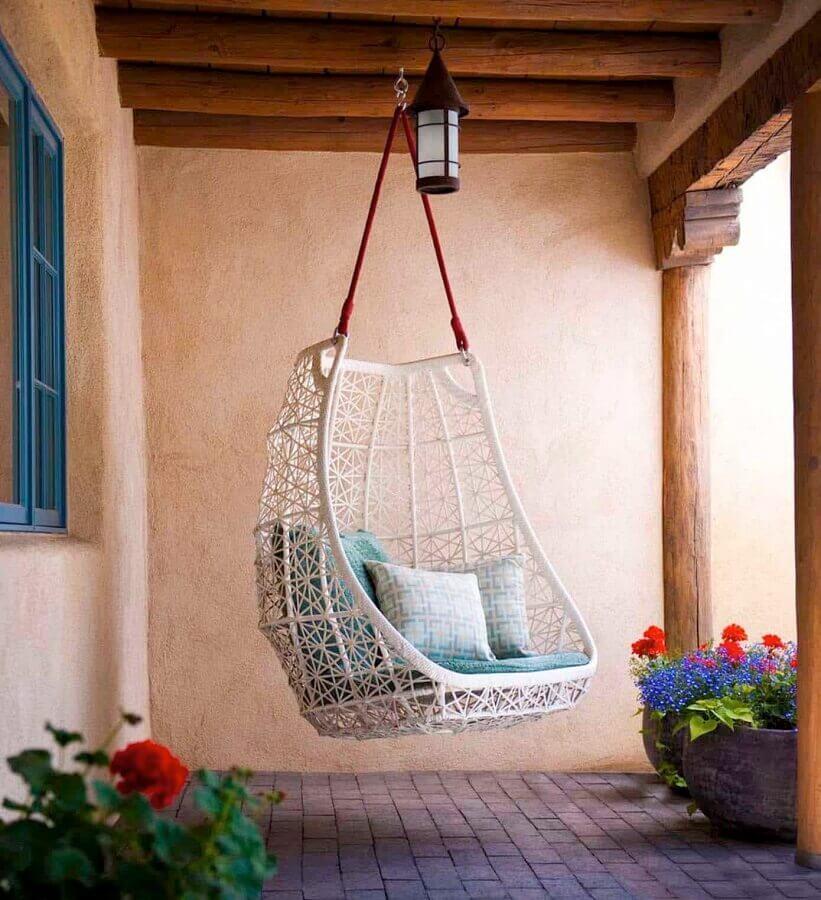 Cadeira de balanço suspensa para varanda rústica decorada com vasos de chão Foto One Kindesign