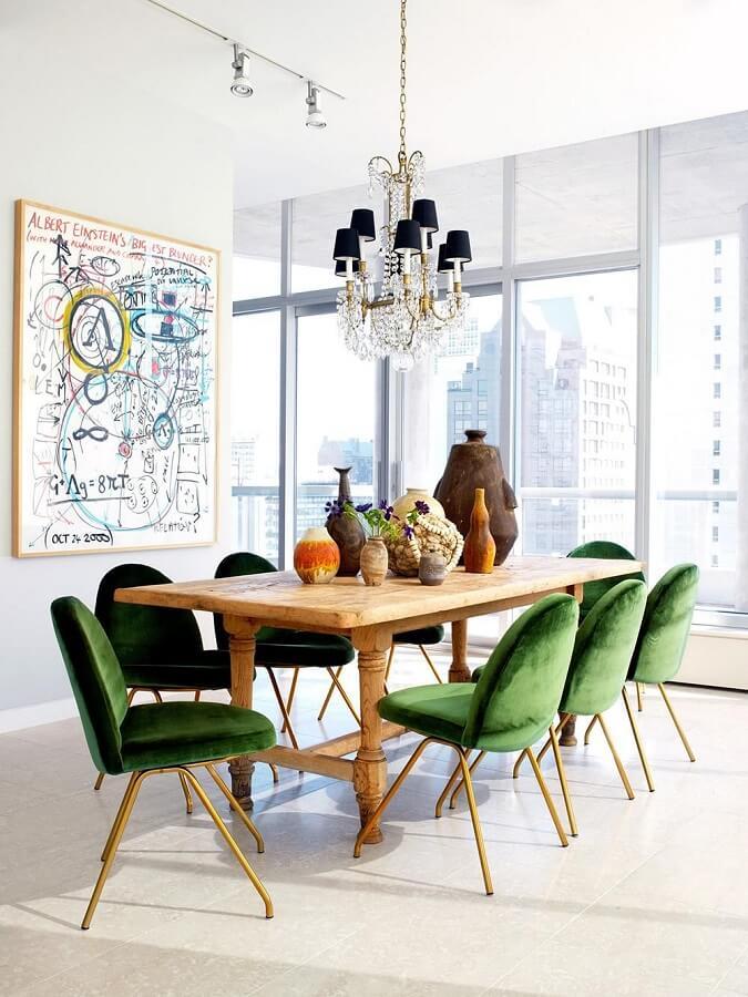 Cadeira veludo verde para sala de jantar branca decorada com mesa de madeira e lustre de cristal  Foto Archdaily