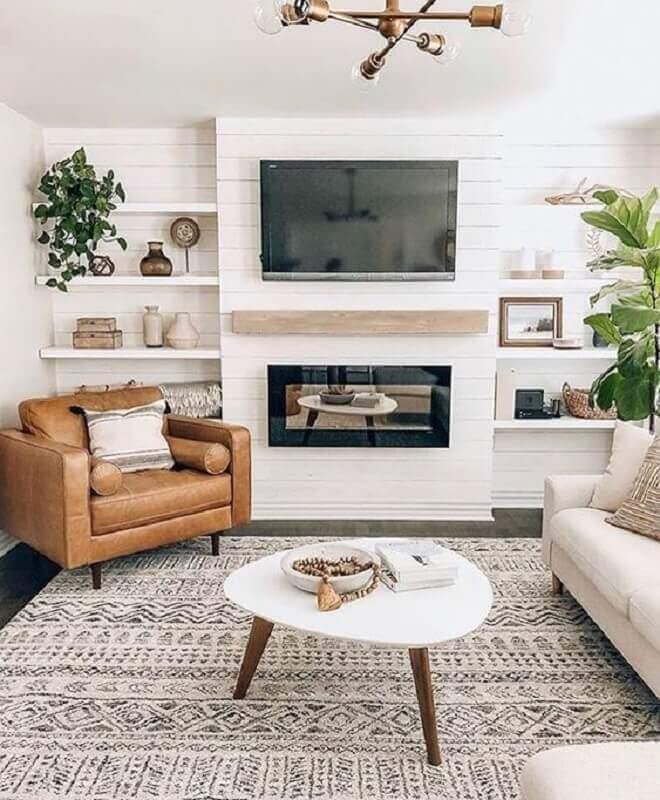 cores claras para sala com lareira decorada com poltrona de couro marrom  Foto Monarch Plank