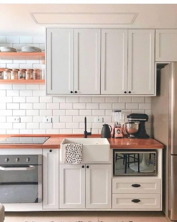 Cozinha branca decorada com armário vintage bancada de madeira e azulejo de cozinha branco simples
