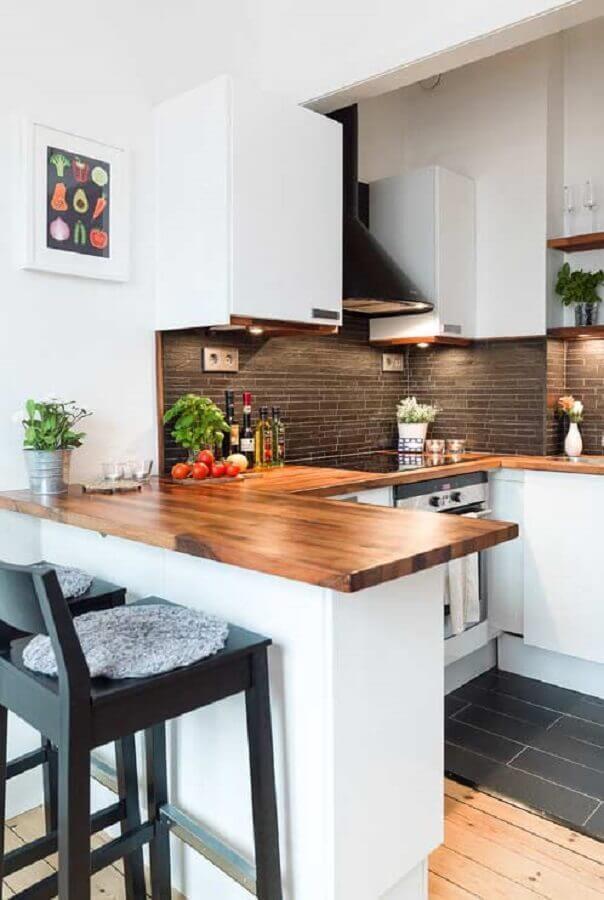 Cozinha estilo americana em U decorada com armários brancos e bancada de madeira Foto Home Fashion Trend