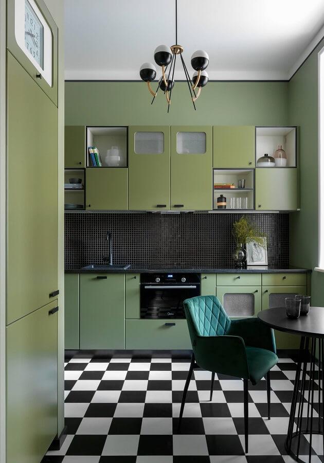 cozinha retrô decorada com piso preto e branco e cadeira estofada verde escuro Foto Decoist
