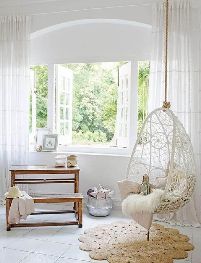 Decoração clean para sala branca com cadeira de balanço suspensa  Foto Sundry Society