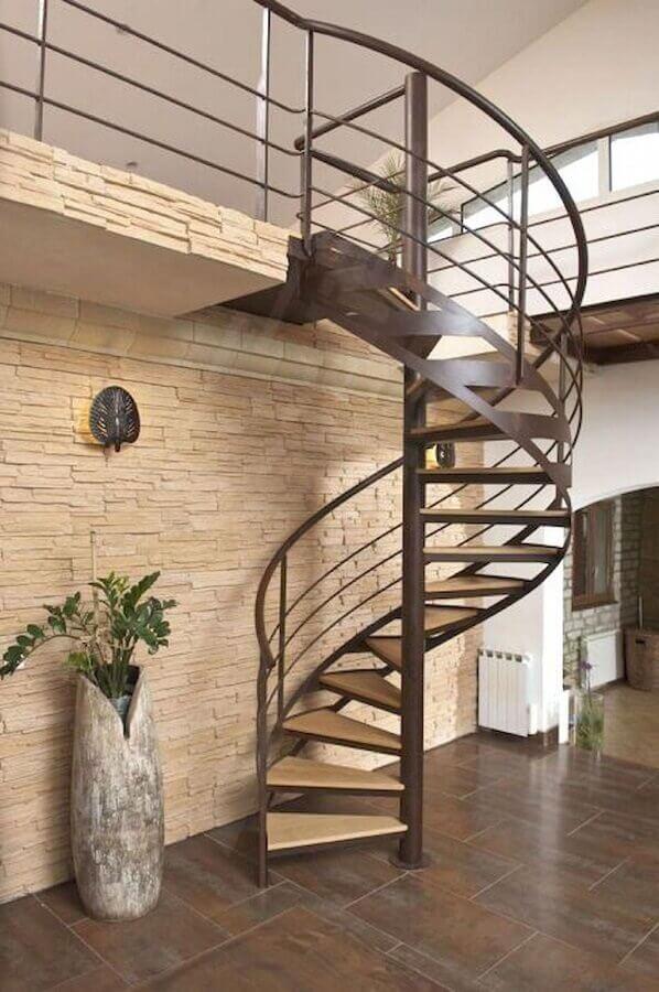 decoração com parede de pedra e escada espiral de ferro e madeira Foto Pinterest