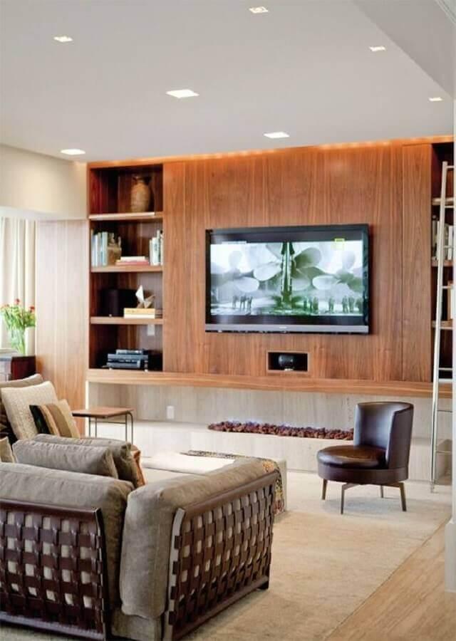 decoração de sala com lareira ecológica grande e painel de madeira Foto Studio1202