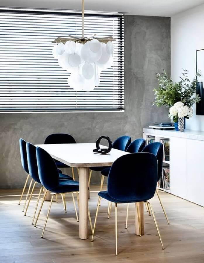 decoração de sala de jantar com parede de cimento queimado e cadeira estofada azul marinho Foto The Design Files