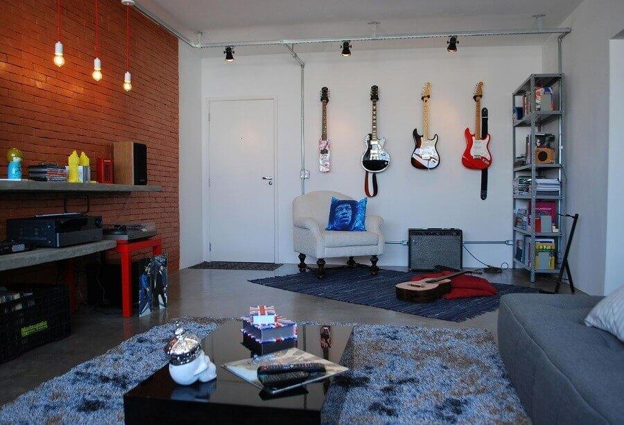 decoração industrial para sala com luminária pendente e guitarras na parede Foto Projética Design e Arquitetura