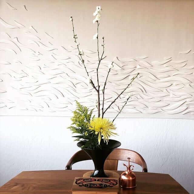 ikebana no vaso preto e flores amarelas
