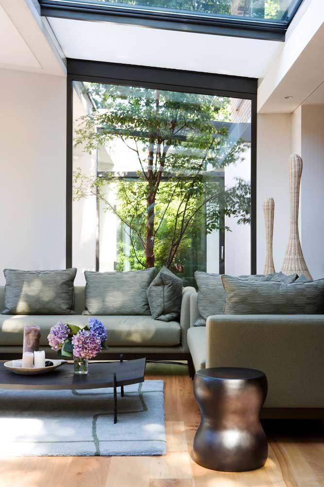 . Sala com sofá estilo industrial e com jardim de inverno