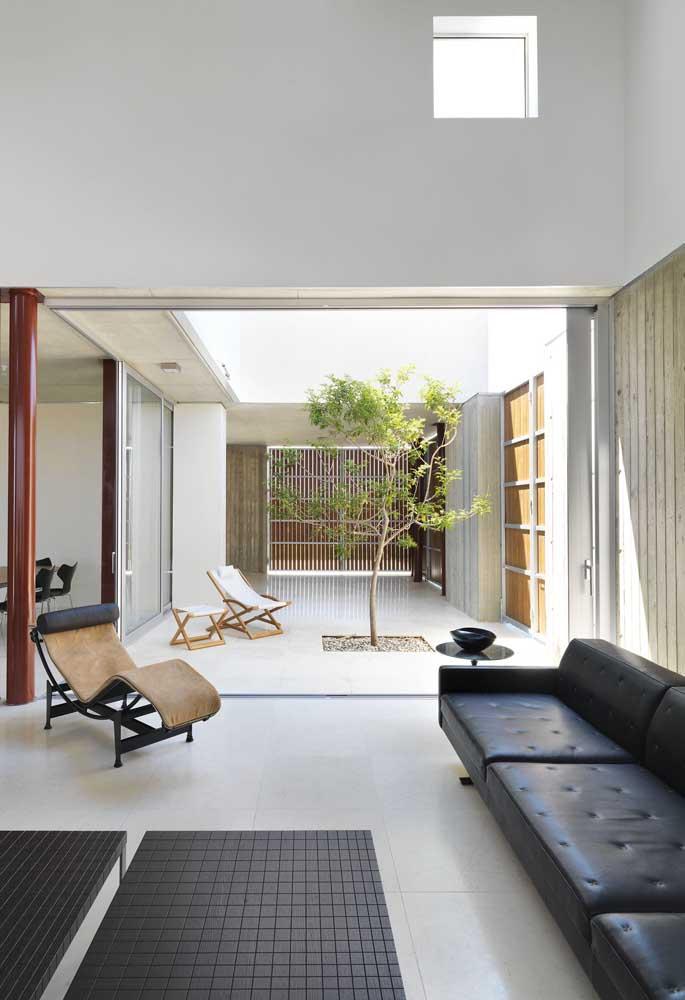 Sala com sofá estilo industrial de couro preto e jardim de inverno ao lado  para iluminar o ambiente