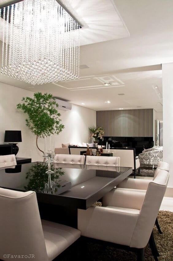 Lustre pendente quadrado de cristal acima da mesa de jantar preta