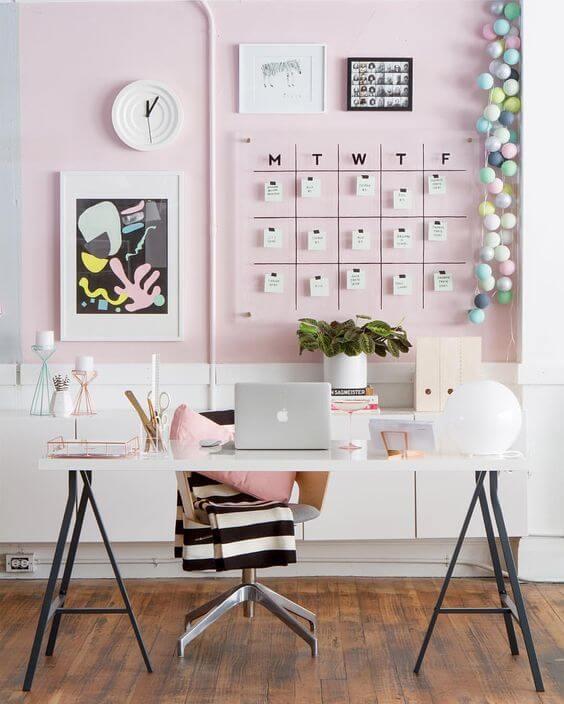 Escritório cor de rosa com cavaletes pretos e mesa branca