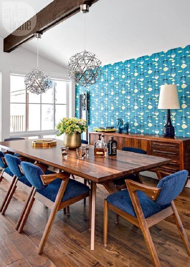 papel de parede e cadeira estofada azul para decoração de sala de jantar com móveis de madeira Foto Curated Interior