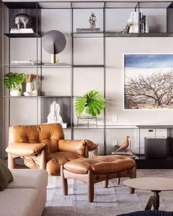 Poltrona capitonê na sala de estar decorada com enfeites para estante vazada