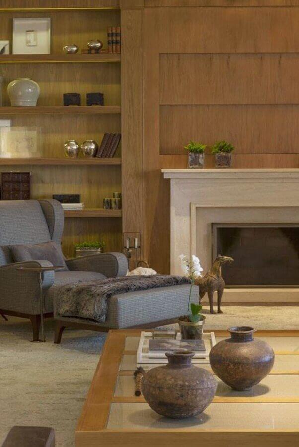 sala com lareira decorada com poltrona cinza e prateleiras de madeira Foto Casa Tres Chic
