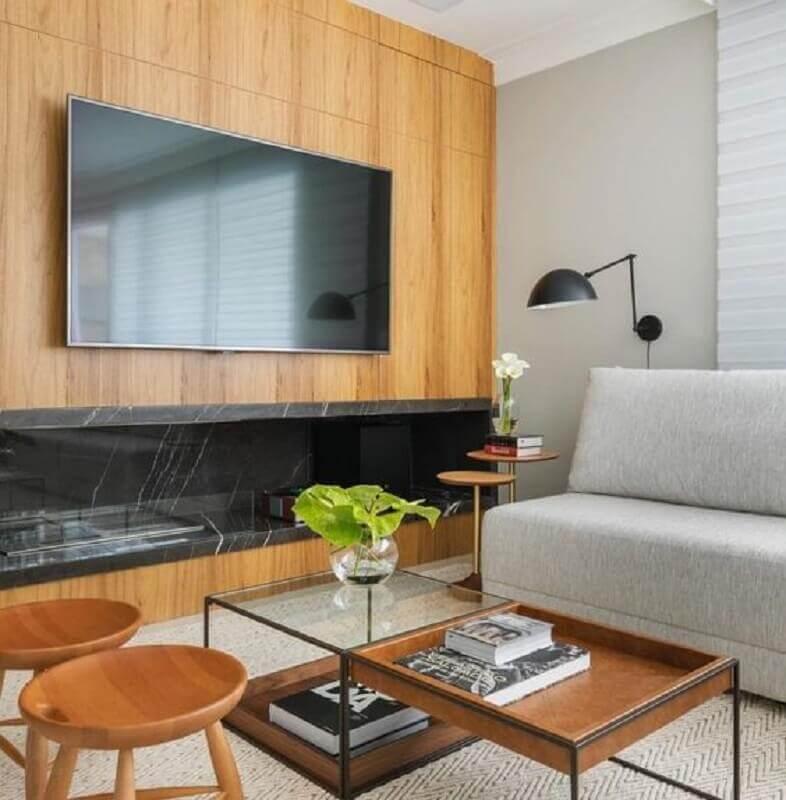 sala com lareira grande decorada com sofá cinza sem braço e revestimento de madeira Foto Pinterest