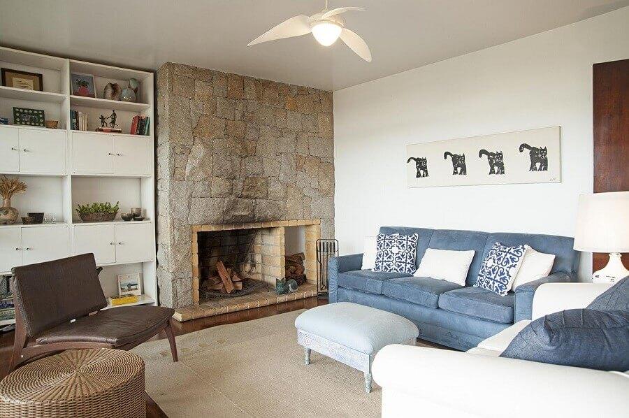sala com lareira rústica decorada com sofá azul Foto Renata Romeiro