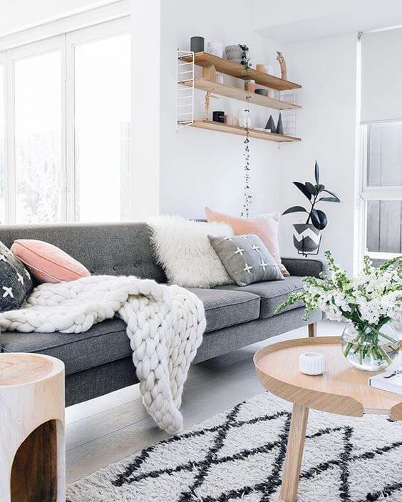 Sala com sofá estilo industrial cinza e decoração branca e rose