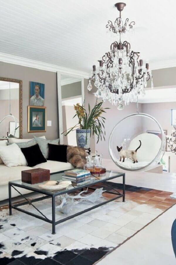 Sala de estar decorada com tapete de couro e cadeira de balanço moderna suspensa Foto Fashionismo