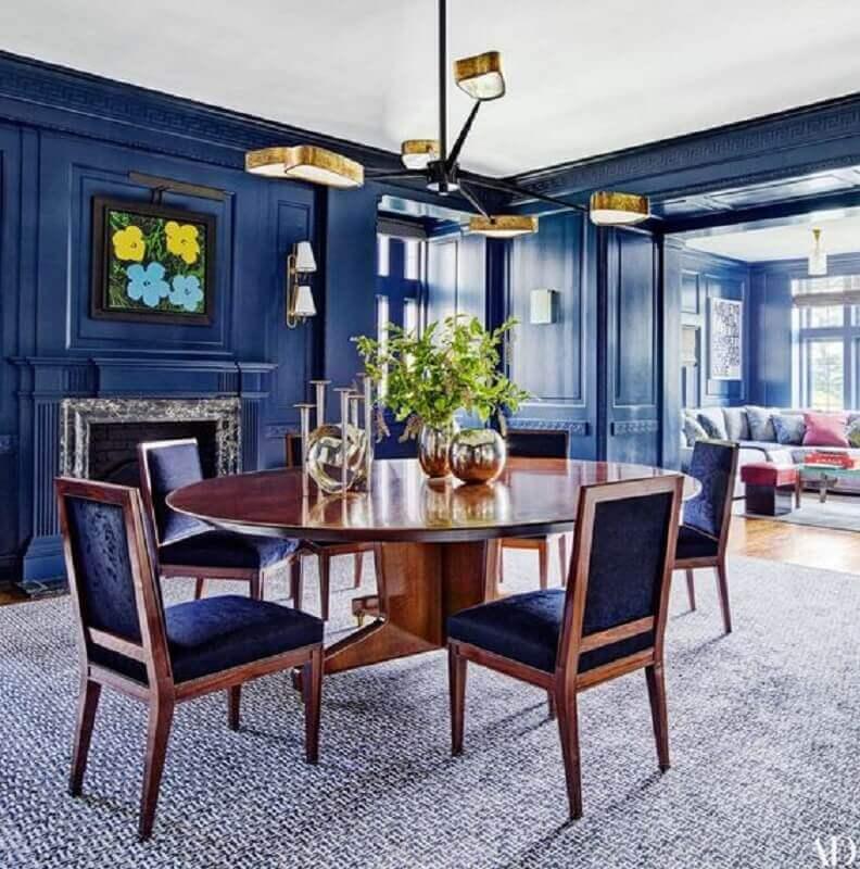 sala de jantar clássica decorada com cadeira estofada azul e lareira Foto Architectural Digest