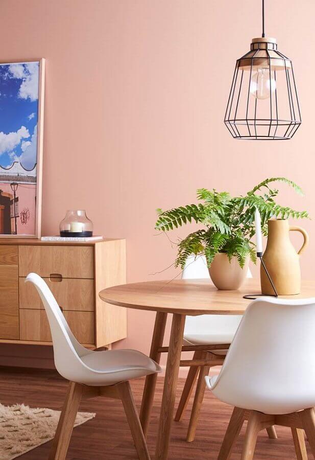 sala de jantar decorada com mesa redonda de madeira e parede rosa chá Foto Pinterest