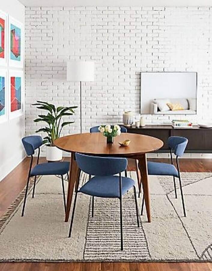 sala de jantar decorada com parede de tijolinho branco e cadeira estofada azul Foto Room & Board