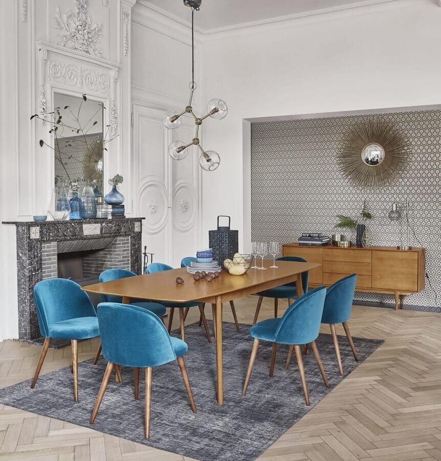 sala de jantar grande decorada com mesa de madeira e cadeira azul estofada Foto Maisons du Monde