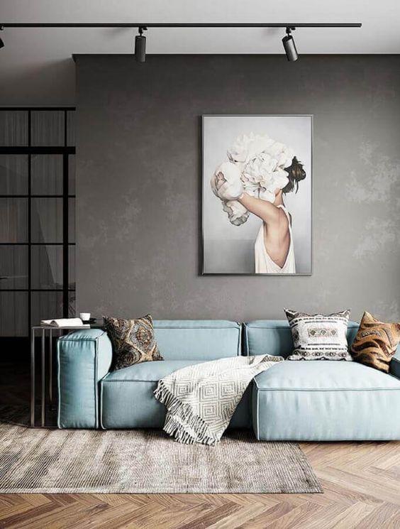 Sala com parede de cimento queimado e sofá industrial azul celeste