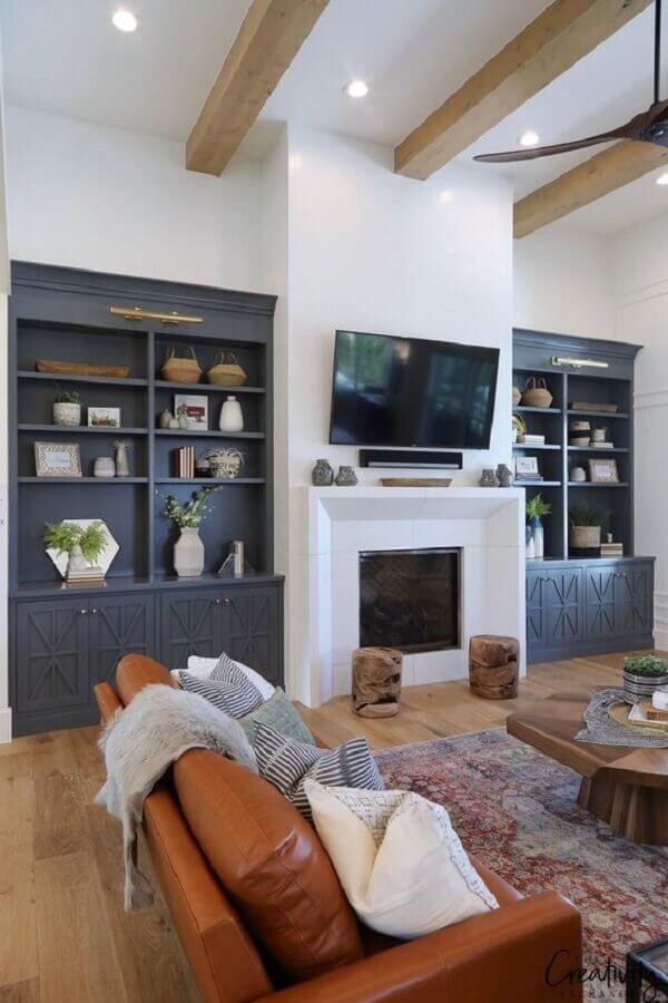 sofá de couro para decoração de sala com lareira e estantes cinza Foto Behance