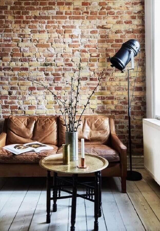 Sala com sofá estilo industrial e papel de parede de tijolinho