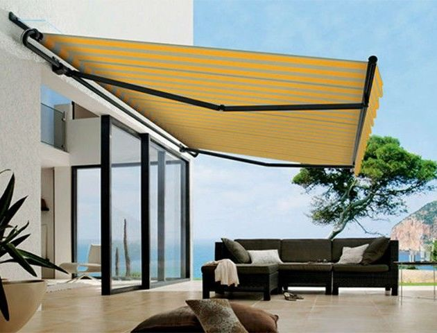 Toldo para varanda moderna com sofás e porta de vidro para sala