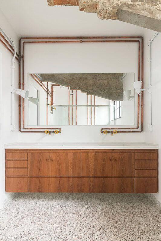 tubulação aparente para decoração de banheiro branco com gabinete de madeira suspenso Foto INÁ Arquitetura