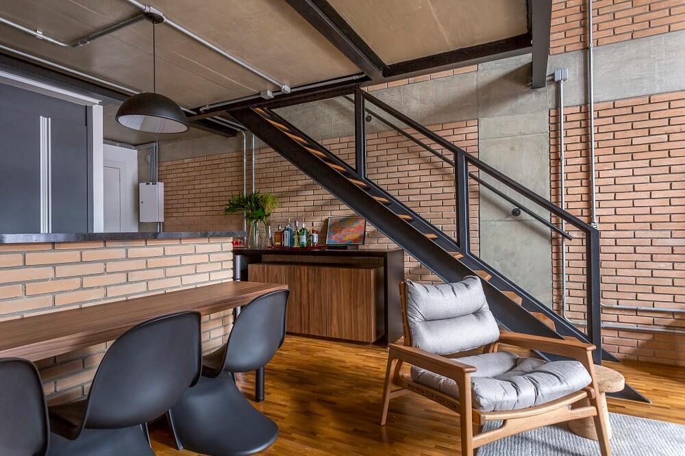 Embaixo da escada e próxima a poltrona de madeira um móvel é usado como aparador bar. Foto: JP Image