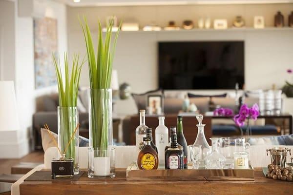 A bandeja decorativa para bar traz um charme a parte para a sala de estar. Projeto de Studio FN