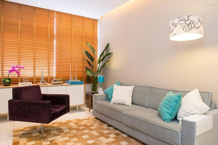 A persiana de madeira retém a entrada de luz natural na sala planejada pequena. Projeto de Marcelo Bastos