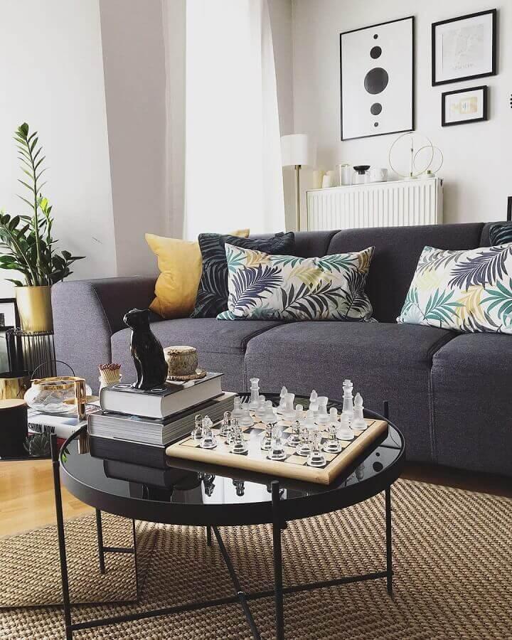 Almofadas para sofá cinza escuro em sala decorada com mesa de centro redonda Foto Corinne Miya